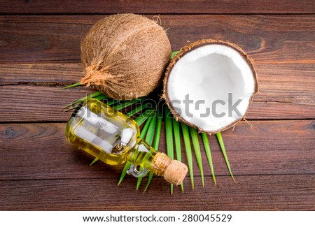 Coconut and coconut oil on wooden table - stock photo