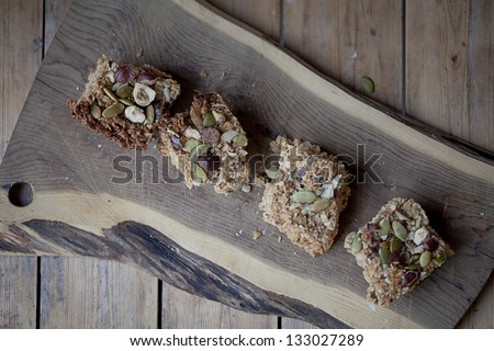 Coconut bars with pumpkin seeds and nuts on a wooden cutting board - stock photo