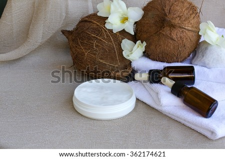 Coconut butter cream. Coconuts,dropper bottles with coconut oil,white towels in the background.