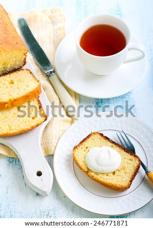 Coconut cake loaf, sliced on plate with cream