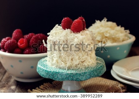 Coconut cake on cake stand topped with raspberries on dark moody background, shallow depth of field - stock photo