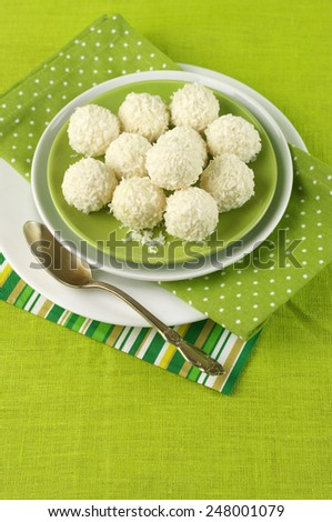 Coconut candies in plate on green cloth. - stock photo