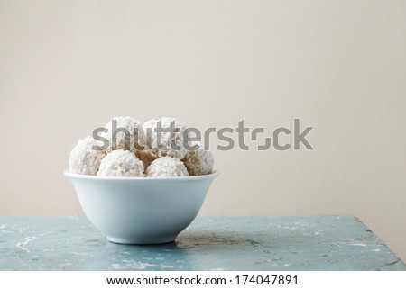 coconut candies in white bowl on vintage wooden table