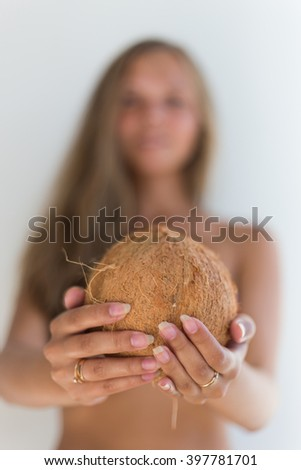 coconut close up in the hand woman background blur