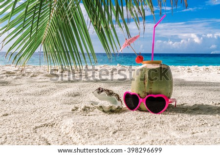 Coconut cocktail, sunglasses and a heart-shaped pearl shell on the beach. - stock photo