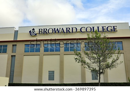 Coconut Creek, FL, USA - January 3, 2015: Exterior of Broward Community College North Campus building and sign with a tree in front and a blue sky with white clouds.