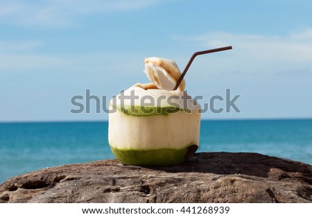 Coconut drink on wood at beach sea summer tropics background