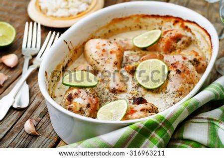 coconut garlic lime chicken legs on a dark wood background. the toning. selective focus - stock photo