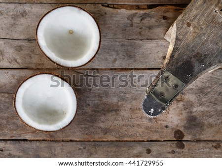 coconut grater and coconut on wood background - stock photo