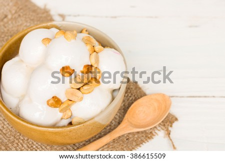 Coconut ice cream with nuts in small bowl with copy space - stock photo