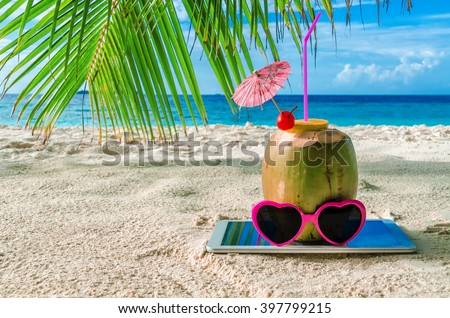 Coconut in sun glasses and a tablet on the sand. Beach accessories - stock photo