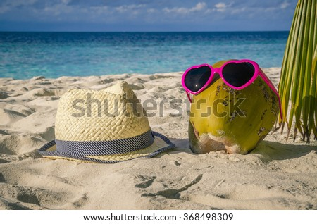 Coconut in sunglasses and straw hat in the sand