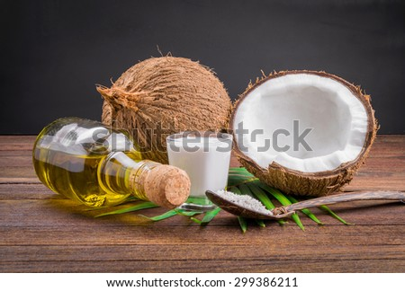 Coconut milk and coconut oil on wooden table - stock photo