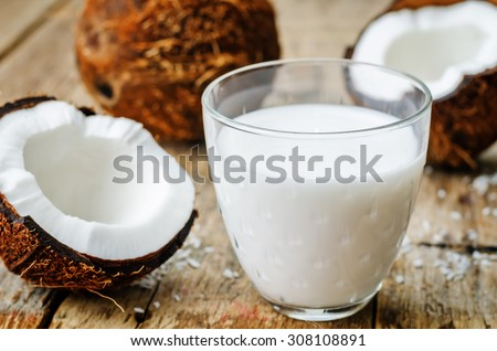 coconut milk and coconuts on a dark wood background. the toning. selective focus - stock photo