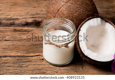 coconut milk and fresh coconuts on old wooden table  - stock photo