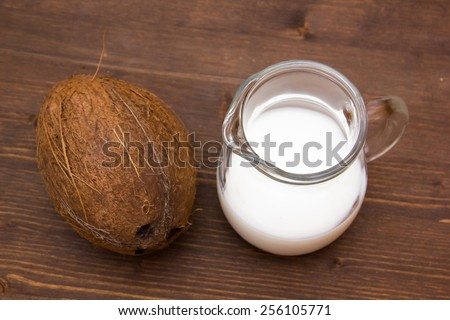 Coconut milk in jug on wooden table seen from above - stock photo