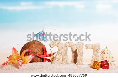 Coconut, number 2017, starfish, flower, tree and Christmas presents in the sand against the sea.