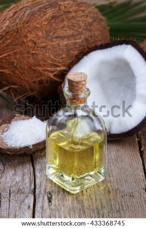 Coconut oil and coconut shell on old wooden background - stock photo
