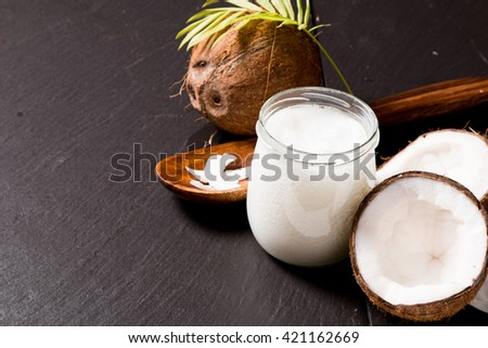 coconut oil and fresh coconuts on black stone background - stock photo
