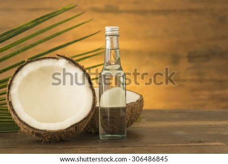 coconut oil and fresh coconuts on wooden table.
