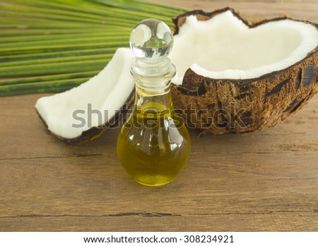 coconut oil and fresh coconuts on wooden table. - stock photo