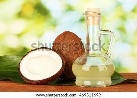 Coconut oil and fresh coconuts on wooden table with light background