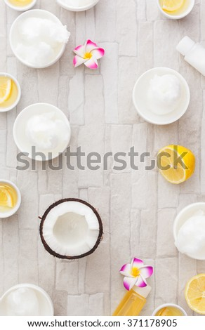 Coconut oil and lemon juice, still life pattern background. Natural ingredient spa treatment, overhead view - stock photo