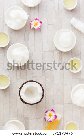 Coconut oil. Bowls of coconut oil and fresh coconut, still life pattern background. Overhead view - stock photo