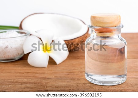 coconut oil in a bottle, background is a half of coconut on the wooden table, isolated - stock photo