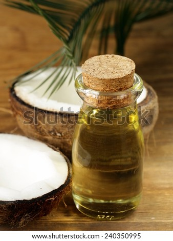 coconut oil in a glass bottle and fresh nuts - stock photo