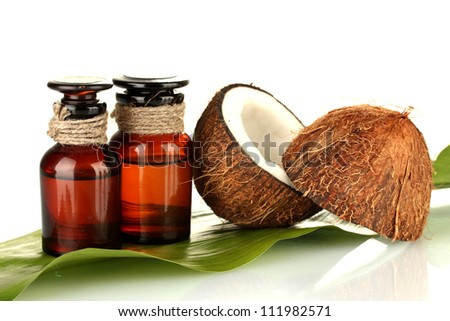 coconut oil in bottles with coconuts on white background - stock photo