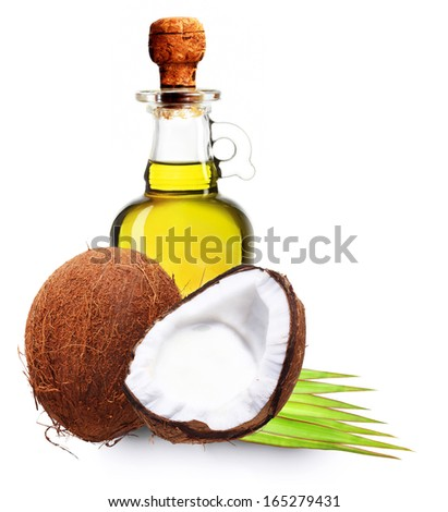 Coconut oil, milk and palm leaves isolated on white. - stock photo