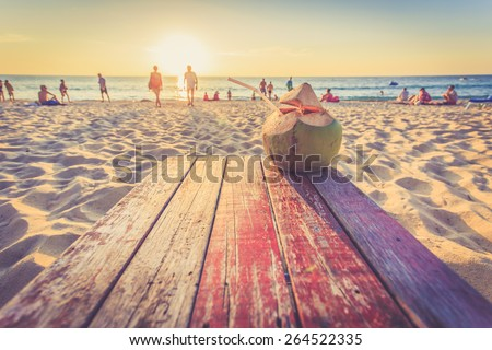 Coconut on the table at sunset beach in Thailand, Vintage filter effect - stock photo