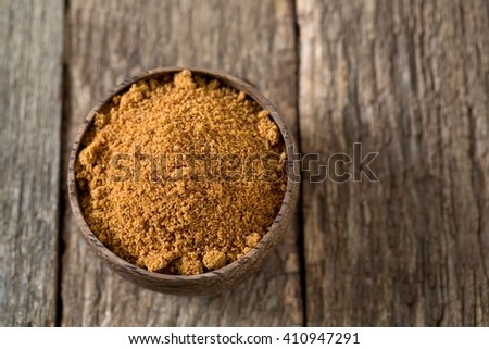 coconut palm sugar on wooden surface - stock photo