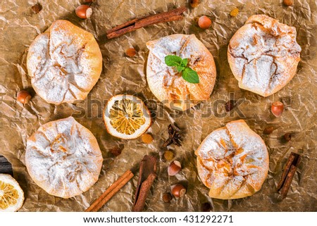 Coconut puff pastries on parchment paper sprinkled with powdered sugar icing, view from above  - stock photo
