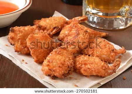 Coconut shrimp on a bar napkin with a mug of beer - stock photo
