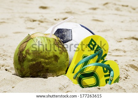 Coconut, Soccer ball and Flip flop with Brazil sign on the sand - stock photo