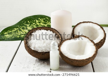 Coconut Spa concept: coconut, coconut oil, sea salt and candle with the scent of coconut on a white background - stock photo