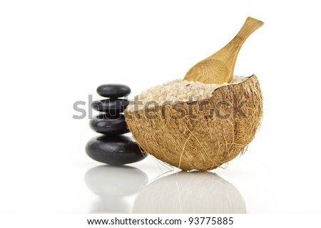 coconut spa salt in coconut shell with wooden spoon and spa stones