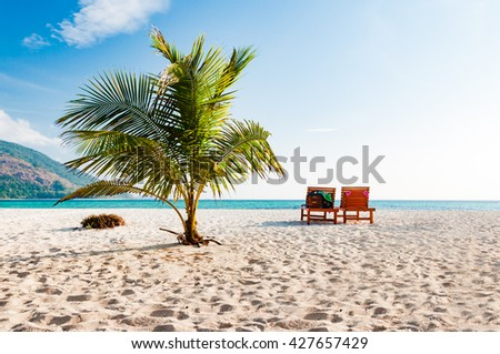 Coconut tree and 2 beach chairs in a sunny blue sky day. A luxury relaxation lifestyle in Phuket, Thailand - stock photo