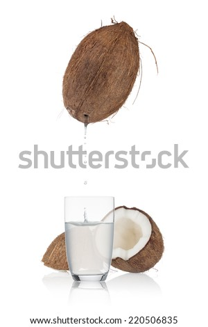 Coconut water droplets from an open coconut into a partly filled glass, with a small splash. Split coconut in the background. On white background.