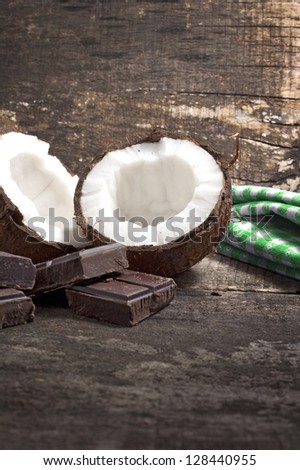 Coconut with chocolate pieces on old wooden background - stock photo