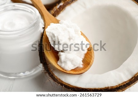 Coconut with coconut oil and jar of cosmetic cream on table close up - stock photo