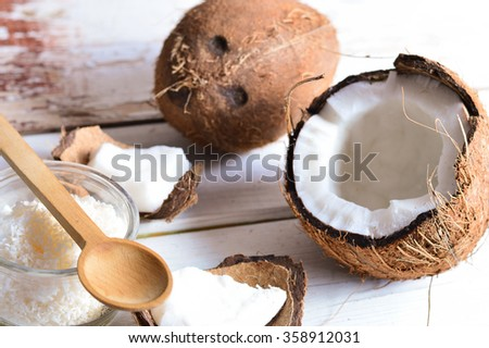 Coconut with coconut oil in jar on white wooden background - stock photo