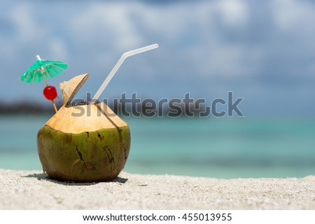 Coconut with drinking straw on beach at the sea