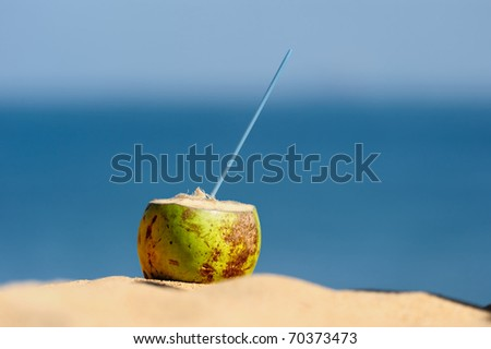 Coconut with drinking straw on the sand at the sea - stock photo