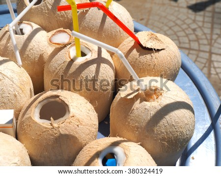 coconut with  drinking straws dipped into the milk - stock photo