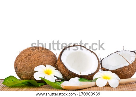 Coconut with green leaf and coconut oil on the wooden spoon - stock photo