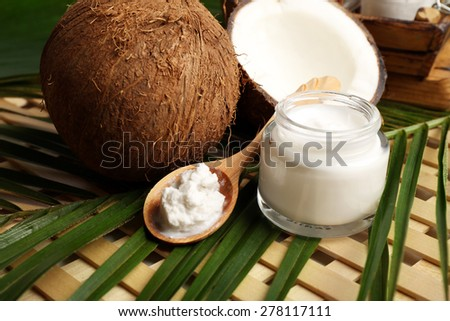 Coconut with leaf and cosmetic cream in jar on wooden background - stock photo