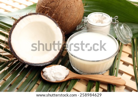 Coconut with leaves and coconut oil in jar on wooden background - stock photo